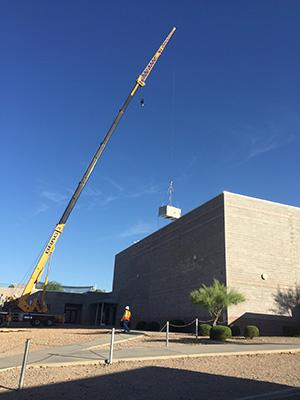 Crane lifing HVAC unites onto roof