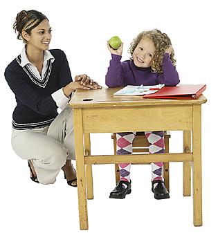 Student giving apple to teacher