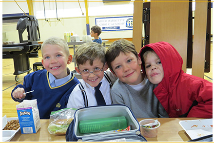 Four happy students posing for a picture at a lunch table