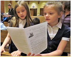 Two school girls singing in church while looking at a music program