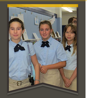 Three FMCS school girls smiling in the hallway