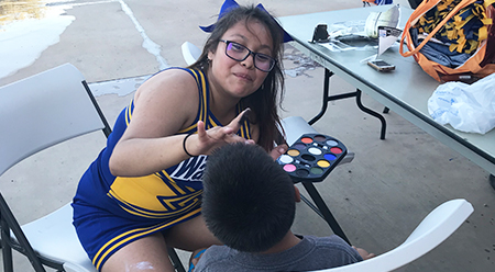 Happy cheerleader adding a face painting to a younger student
