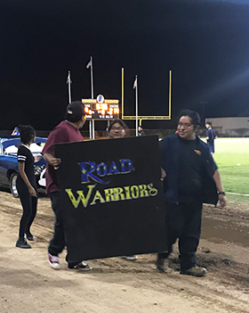 Three student holding the ROAD WARRIORS banner during Homecoming