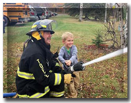 student and fireman with firehose