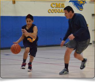 Two students playing basketball