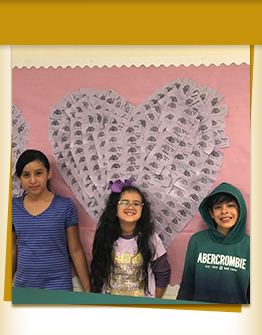 Three happy students in front of bulletin board with hearts