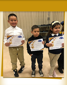 Three happy elementary students holding awards