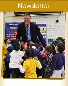 Elementary students welcoming a visitor in the classroom