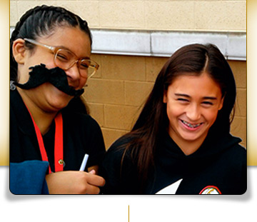 students laughing with fake moustache