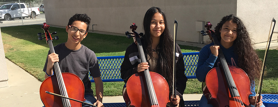 Three students holding cello