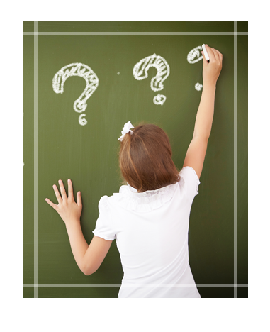 Student Writing Question Marks on Chalkboard